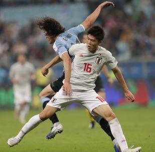 O jogador do Uruguai, Edinson Cavani, divide a bola com o jogador do Japão Takehiro Tomiyasu durante jogo do Grupo C da Copa América, em Porto Alegre.