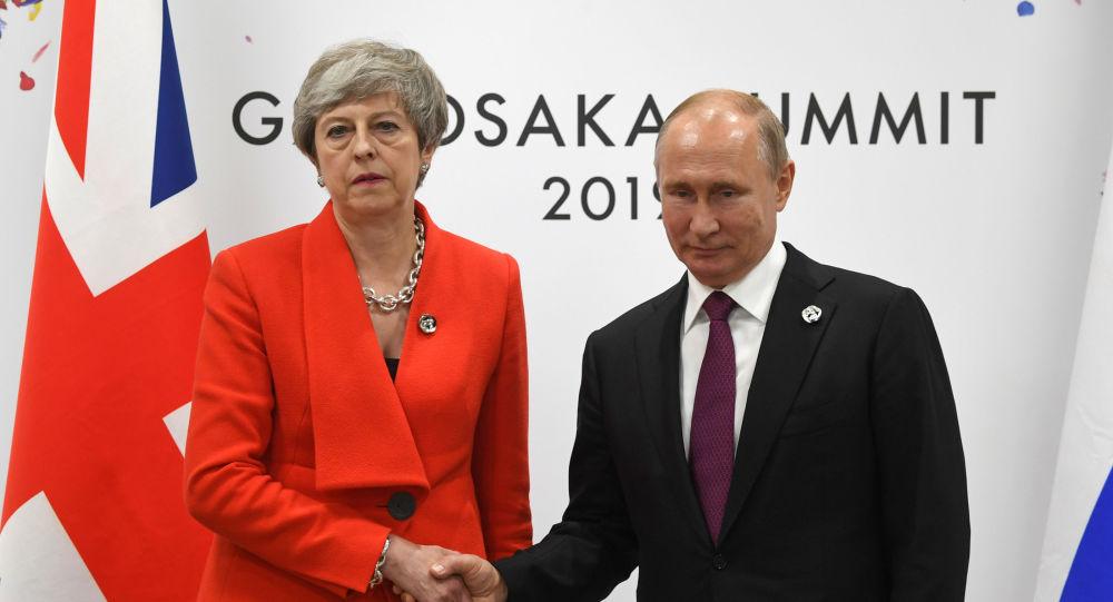 Premiê britânica Theresa May posa ao lado do presidente russo Vladimir Putin no G20, que acontece no Japão