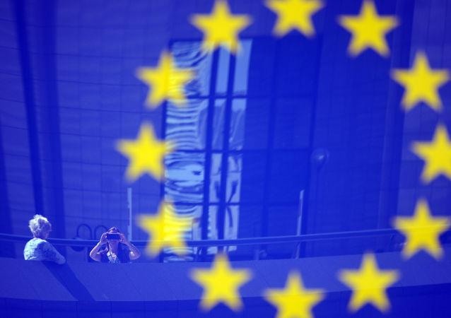 Turistas refletidos em um logotipo da UE.