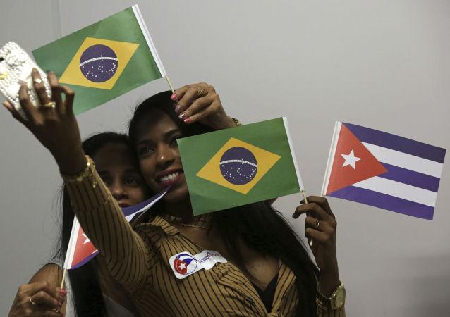 Médicas cubanas seguram bandeiras do Brasil e de Cuba  no aeroporto de Brasília antes de voltarem para seu país de origem, em 22 de novembro de 2018.