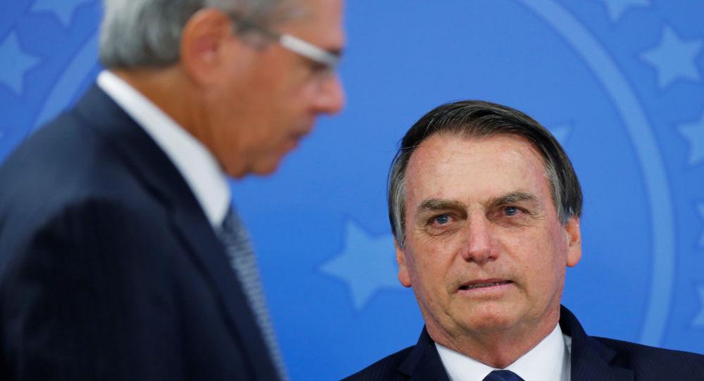 O ministro da Economia, Paulo Guedes, passa em frente ao presidente do Brasil, Jair Bolsonaro (PSL) no Palácio do Planalto em 16 de julho de 2019.