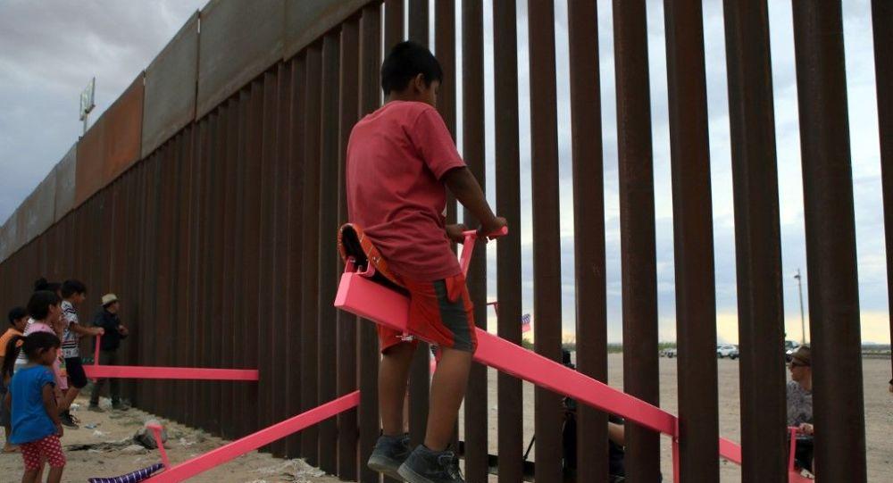 Arquiteto instala gangorras em muro na fronteira entre México e EUA e crianças brincam separadas pela barreira. Foto em 28 de julho de 2019.