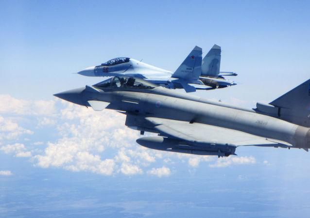 Caça Typhoon da Força Aérea do Reino Unido (em primeiro plano) segue um caça Su-30 Flanker russo