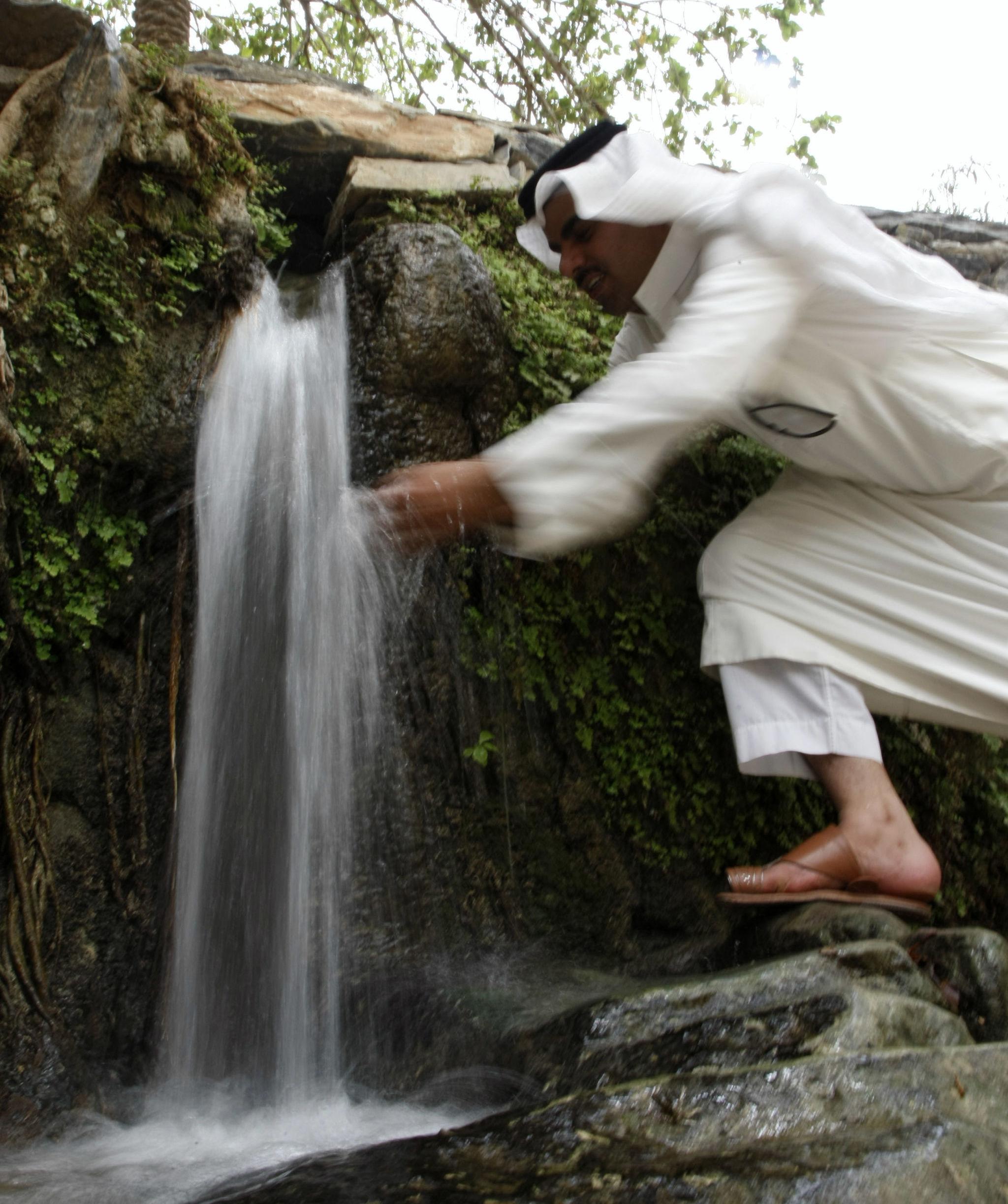 Saudita bebe água após visitar o vilarejo de Dhi Ain a sudoeste de Riad em 13 de maio de 2009