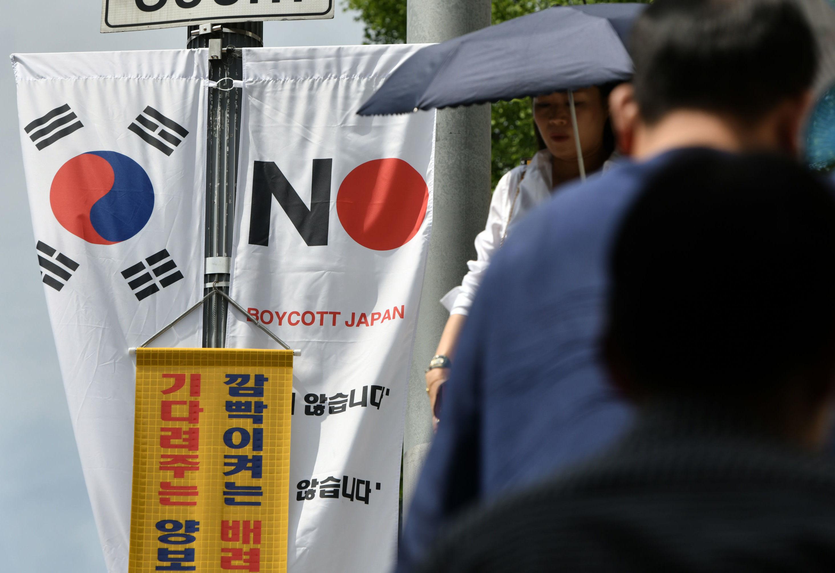 Pedestres passam por anúncio com as bandeiras da Coreia do Sul e do Japão