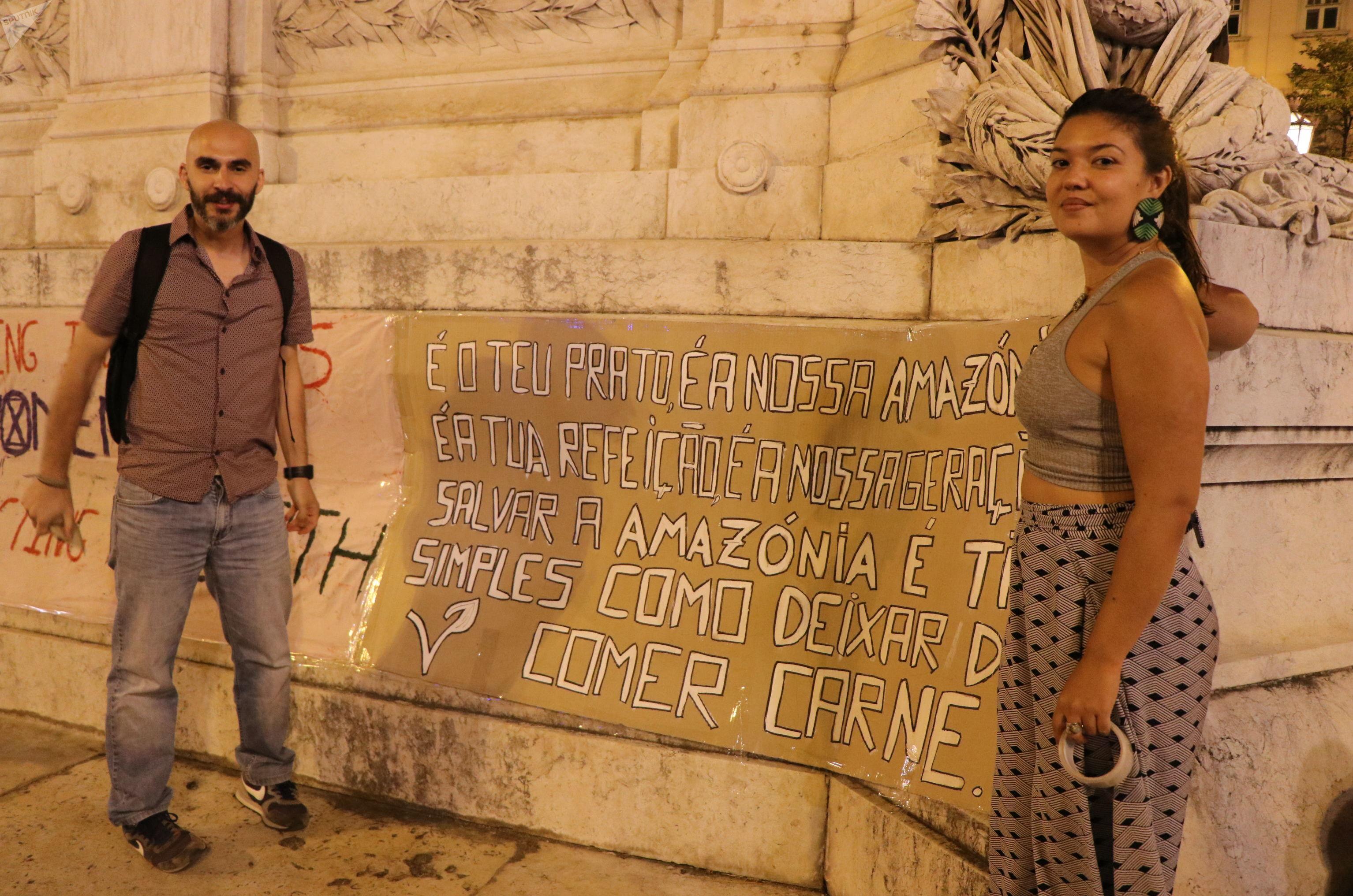 Os ativistas Paulo Muniz e Illa Branco seguram um cartaz durante protesto pela Amazônia em Lisboa. Foto de 23 de agosto de 2019.