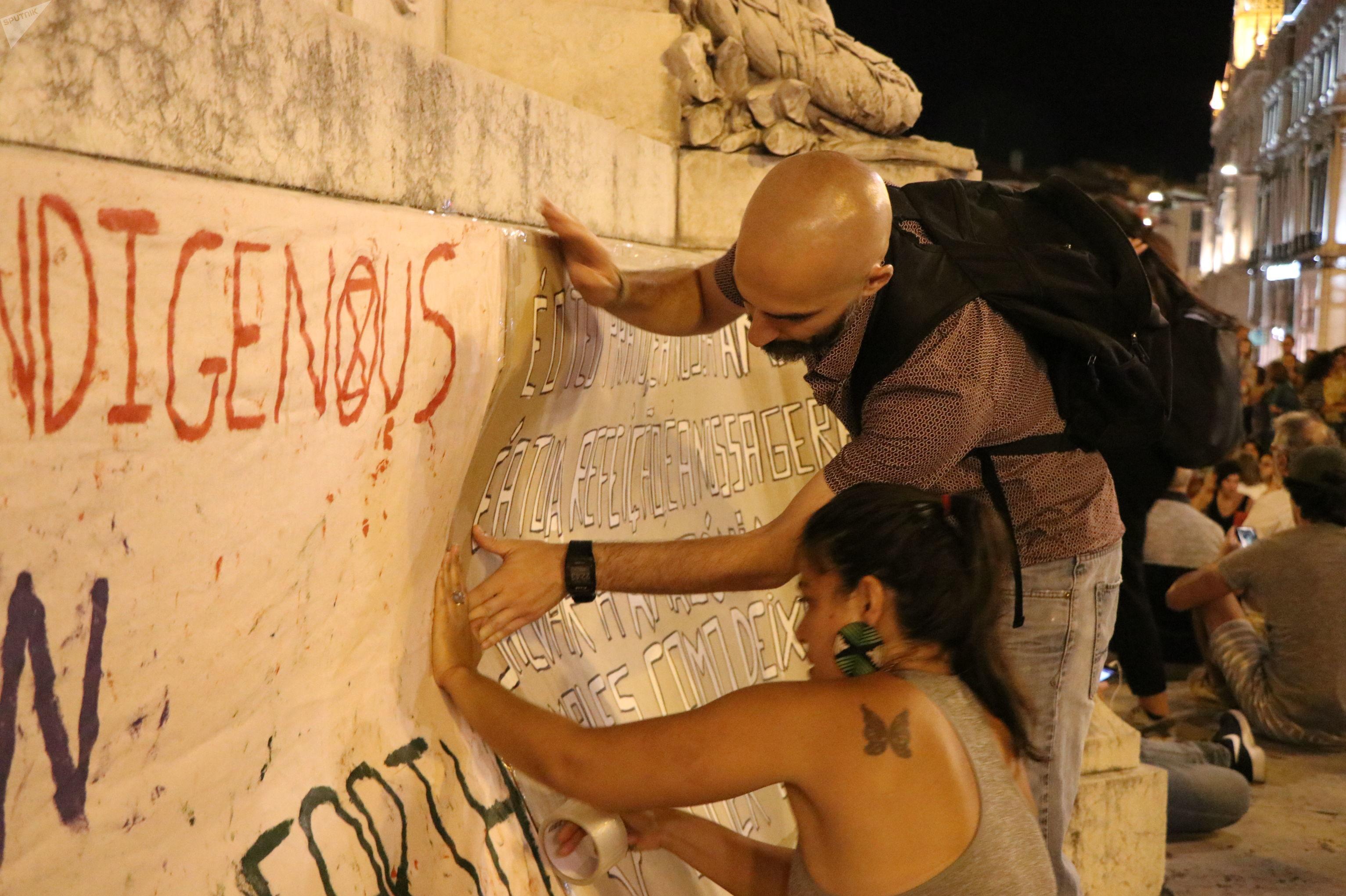 Durante protesto pela Amazônia em Lisboa, os ativistas Paulo Muniz e Illa Branco colam um cartaz em um prédio. Foto de 23 de agosto de 2019.