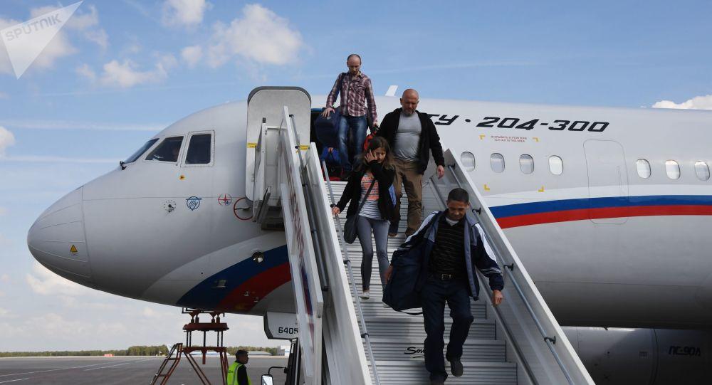 Pessoas libertas na sequência do acordo entre a Rússia e a Ucrânia descendo do avião Tu-204 no Aeroporto Internacional Vnykovo, em Moscou