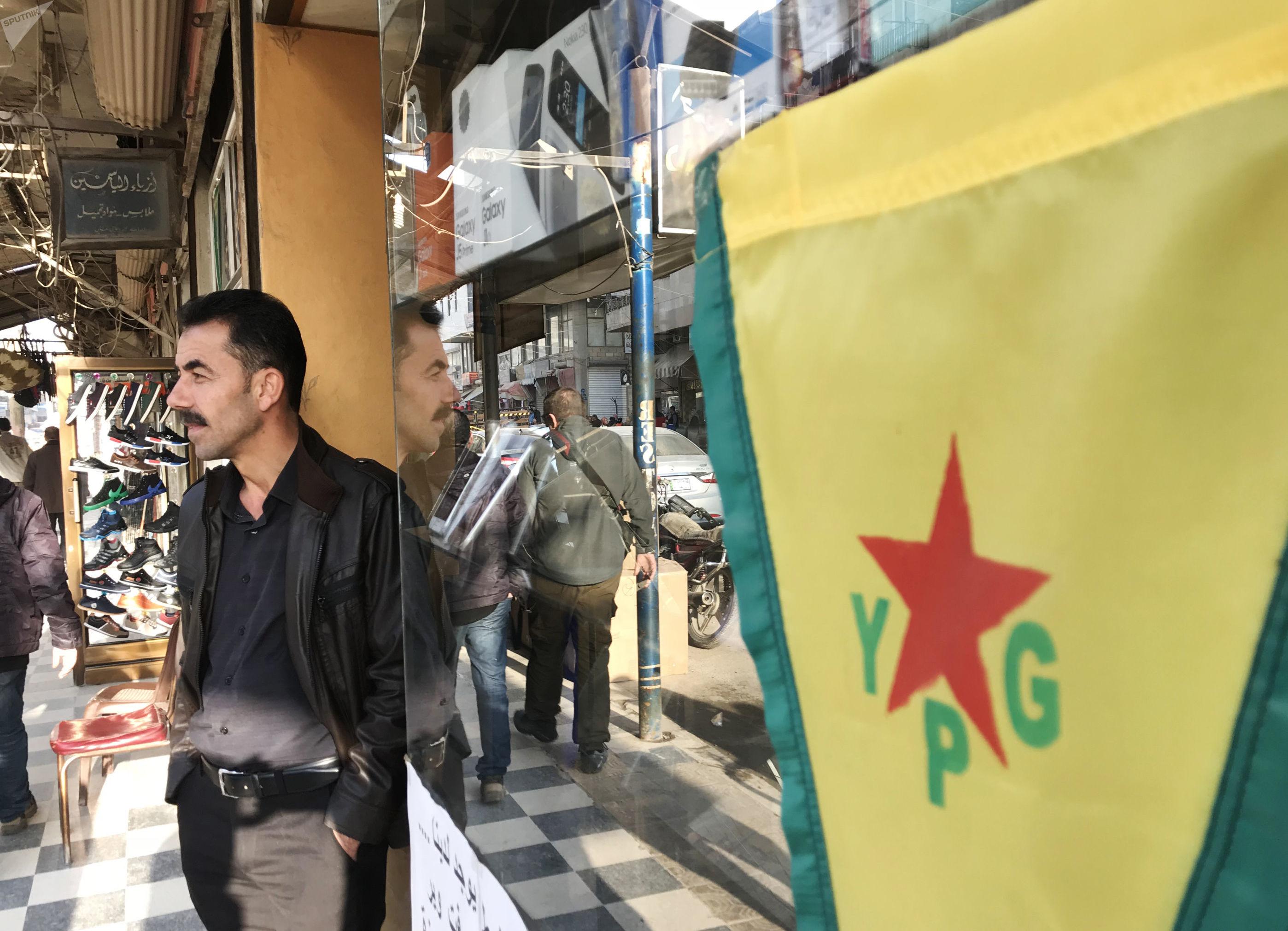 Bandeira da milícia curda YPG na rua central da cidade de Afrin, na Síria