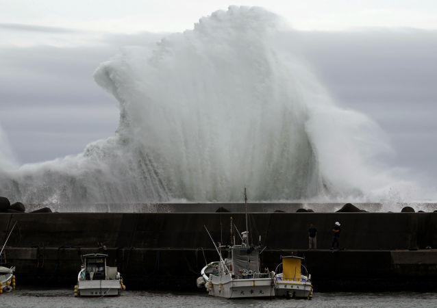 Um homem olha para barcos de pesca enquanto uma onda explode ao fundo na cidade portuária de Kiho, no Japão, em 11 de outubro de 2019. O tufão Hagibis passa pelo país causando alterações climáticas e evacuações.