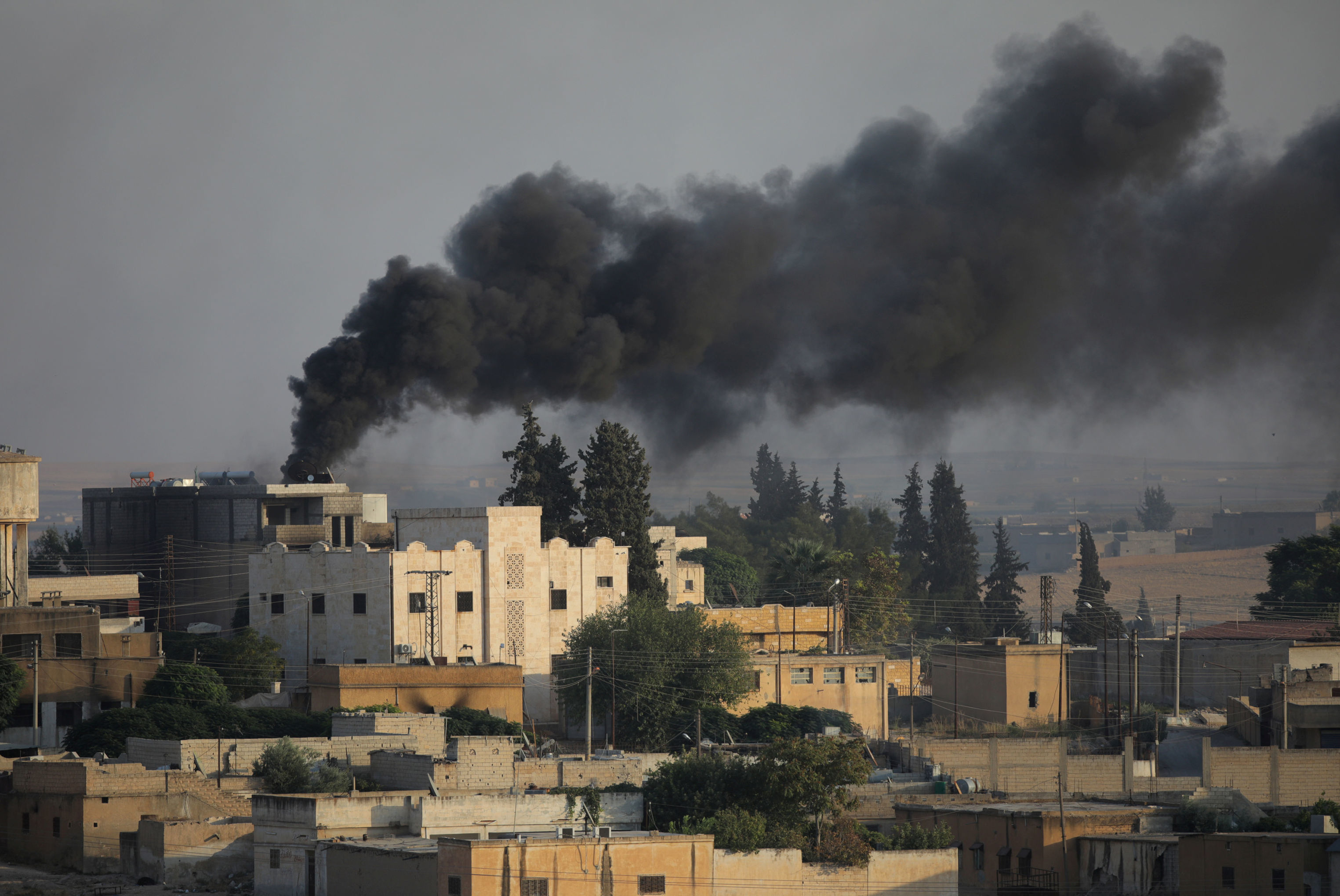 Fumaça subindo sobre a cidade fronteiriça síria de Tel Abyad vista da cidade turca de Akcakale