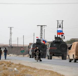 Bandeiras da Rússia e da Síria em veículos militares perto da cidade de Manbij