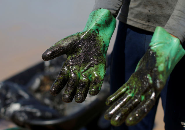 Homem mostra suas luvas cobertas por petróleo ao trabalhar na limpeza da Praia de Coruripe, em Alagoas.