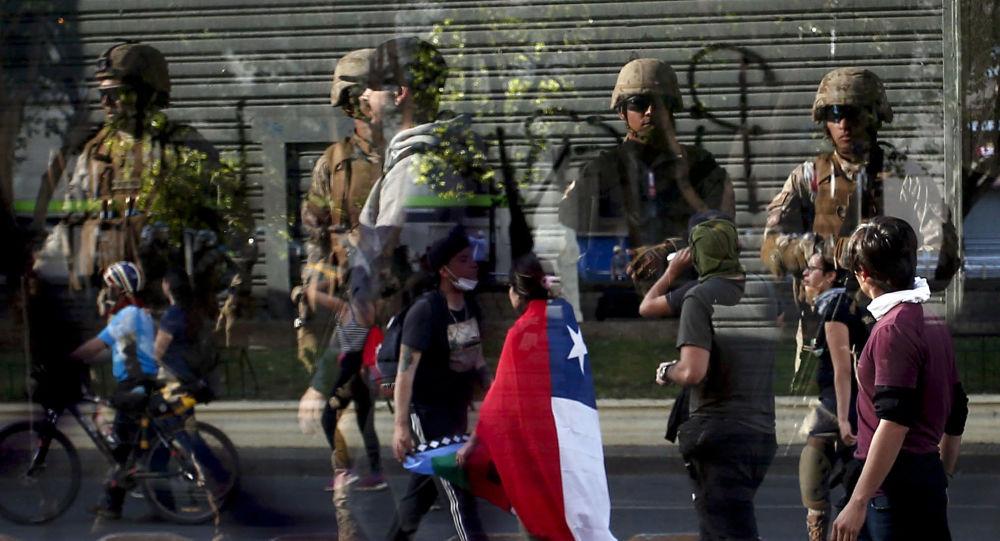 Reflexo de soldados em vidraça enquanto manifestantes passam em frente durante protestos no Chile em 21 de outubro de 2019.
