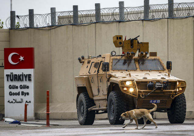 Veículo militar da Turquia retorna à fronteira do seu país, no posto de fronteira de Jarabulus, a 30km de Manbij
