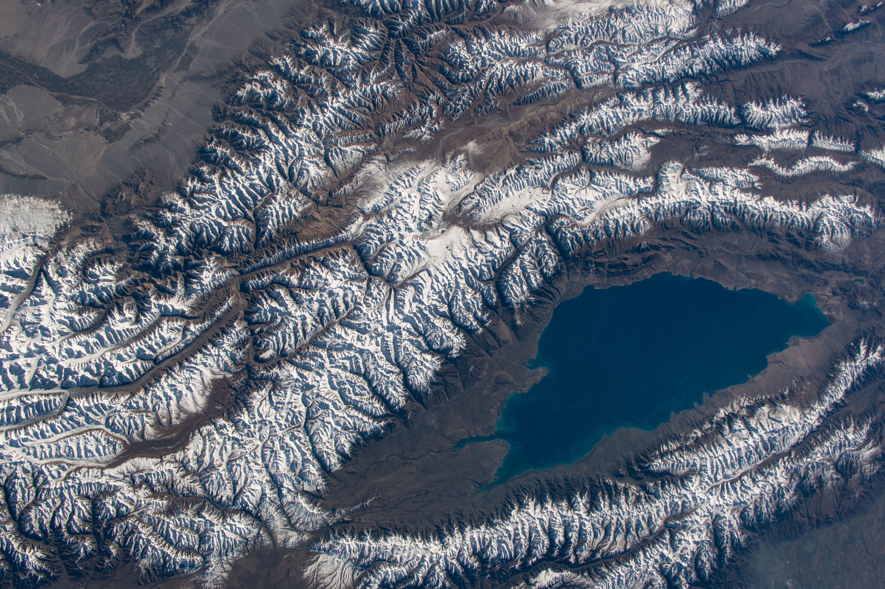 Lago Issyk-Kul, no Quirguistão, Ásia Central, rodeado pelas montanhas de Tian Shen, cobertas de neve