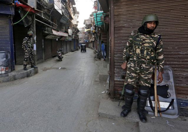 Pessoal da força de segurança indiana monta guarda em frente a lojas fechadas em uma rua de Srinagar, Caxemira