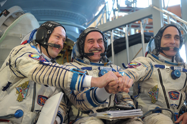 Cosmonautas russos Pavel Vinogradov e Aleksandr Misurkin se preparam para lançamento da nave Soyuz TMA-M, junto com o astronauta norte-americano Christopher Cassidy (à esquerda)