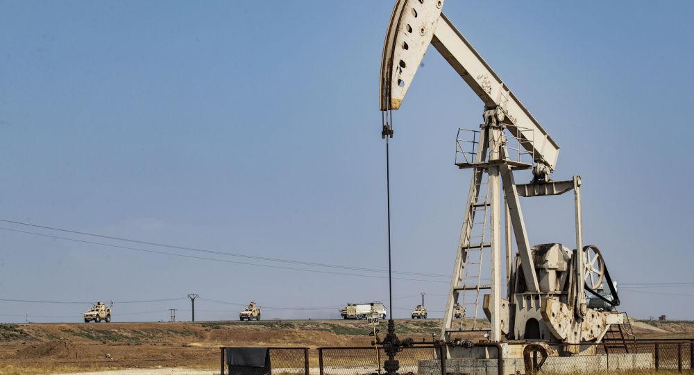 Um comboio de veículos militares dos EUA, vindo do norte do Iraque, passa por uma bomba de petróleo na zona rural da cidade de Qamishli, no nordeste da Síria, em 26 de outubro de 2019