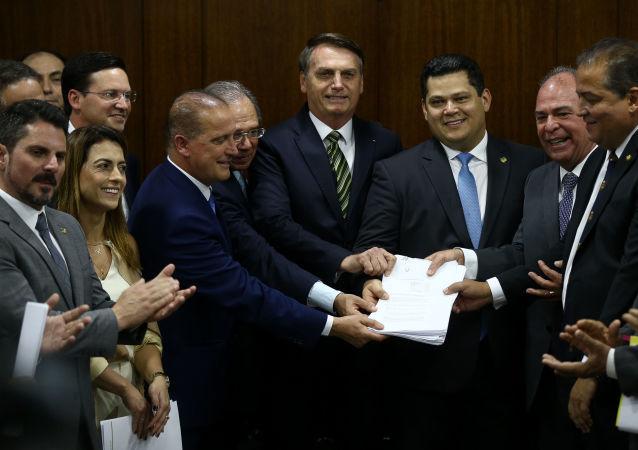 O presidente Jair Bolsonaro, acompanhado dos ministros Paulo Guedes (Economia) e Onyx Lorenzoni (Casa Civil), entrega ao presidente do senado, Davi Alcolumbre (DEM-AP), um conjunto de propostas para dar maior flexibilidade ao Orçamento, ações para elevar os repasses de recursos a estados e municípios (pacto federativo), além da revisão de cerca de 280 fundos públicos. O ato foi no gabinete da presidência do Senado.