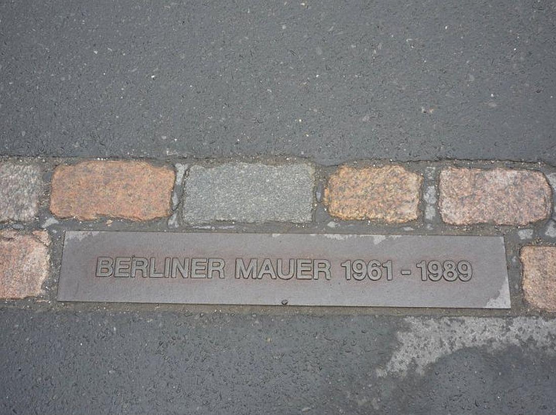 Placa em uma das ruas de Berlim relembra por onde passava o muro que dividia as duas Alemanhas