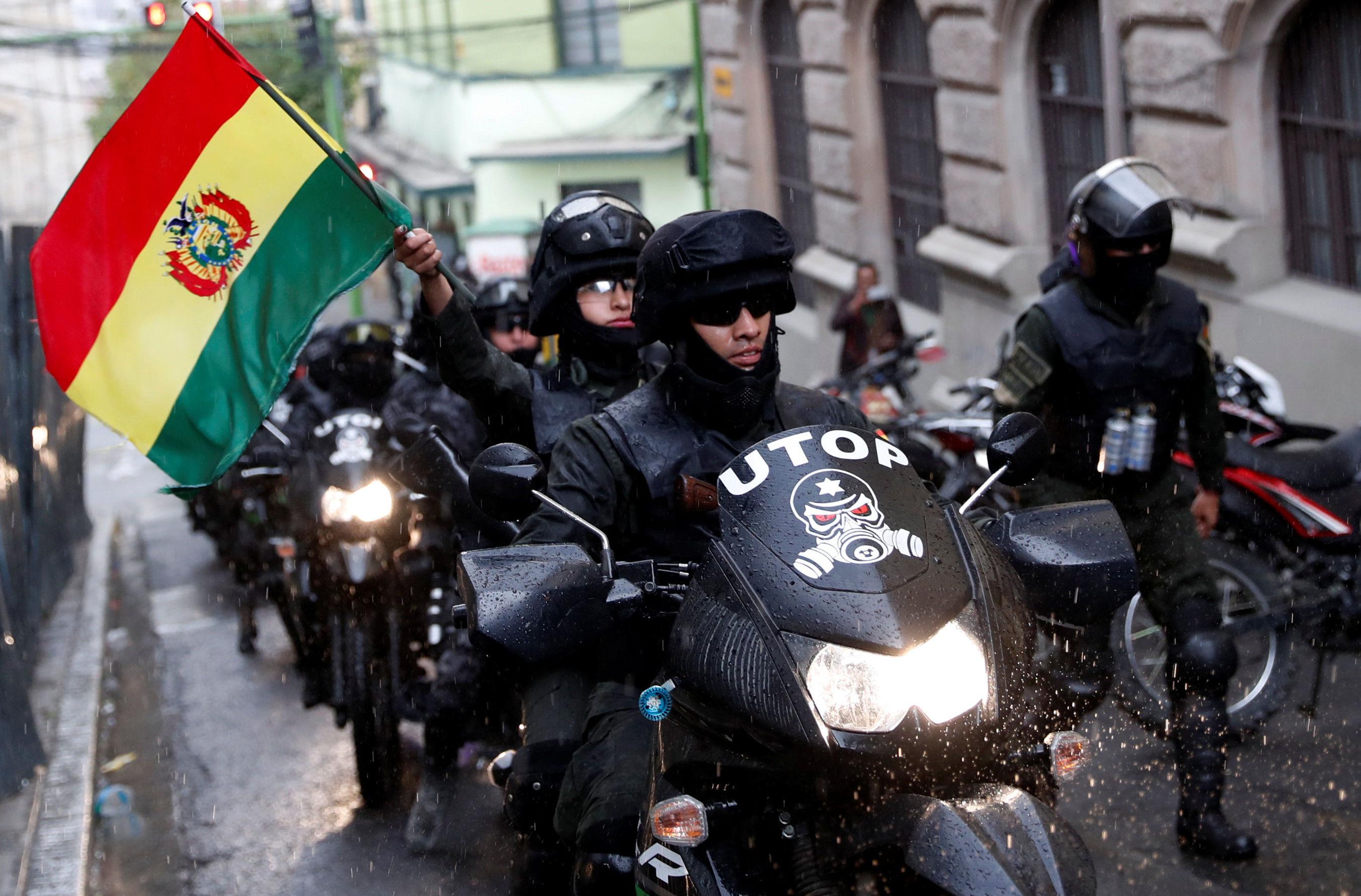 Policiais bolivianos empunham a bandeira do país. As forças de segurança são acusadas de não reagir a ataques contra casas de familiares dos membros do governo, inclusive a da irmã de Evo Morales