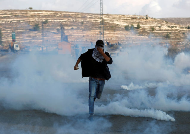 Manifestante palestino corre das forças israelenses durante protesto próximo a um assentamento de Israel na Cisjordânia