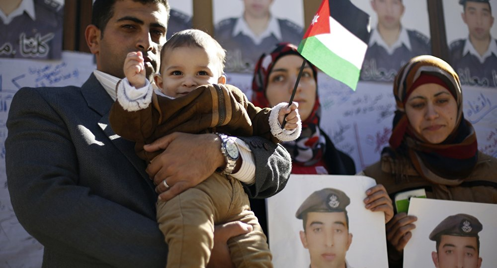 Familiares do piloto jordaniano executado pelo Estado Islâmico seguram cartazes com seu retrato