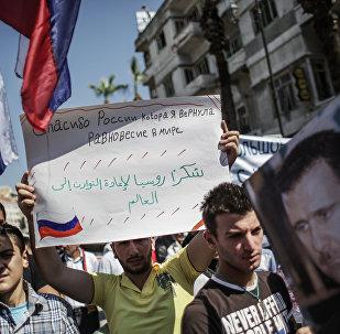 Homem segura o cartaz que diz Obrigado, Rússia, que restaurou o equilíbrio no mundo durante a manifestação na Síria em apoio da Rússia (foto de arquivo)