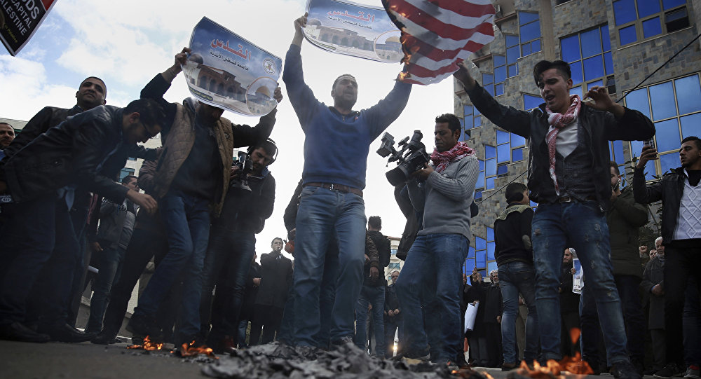 Palestinian protesters chant angry slogans as one burns a representation of the American flag, during a protest against the U.S. decision to recognize Jerusalem as Israel's capital, in Gaza City Thursday, Dec. 7, 2017