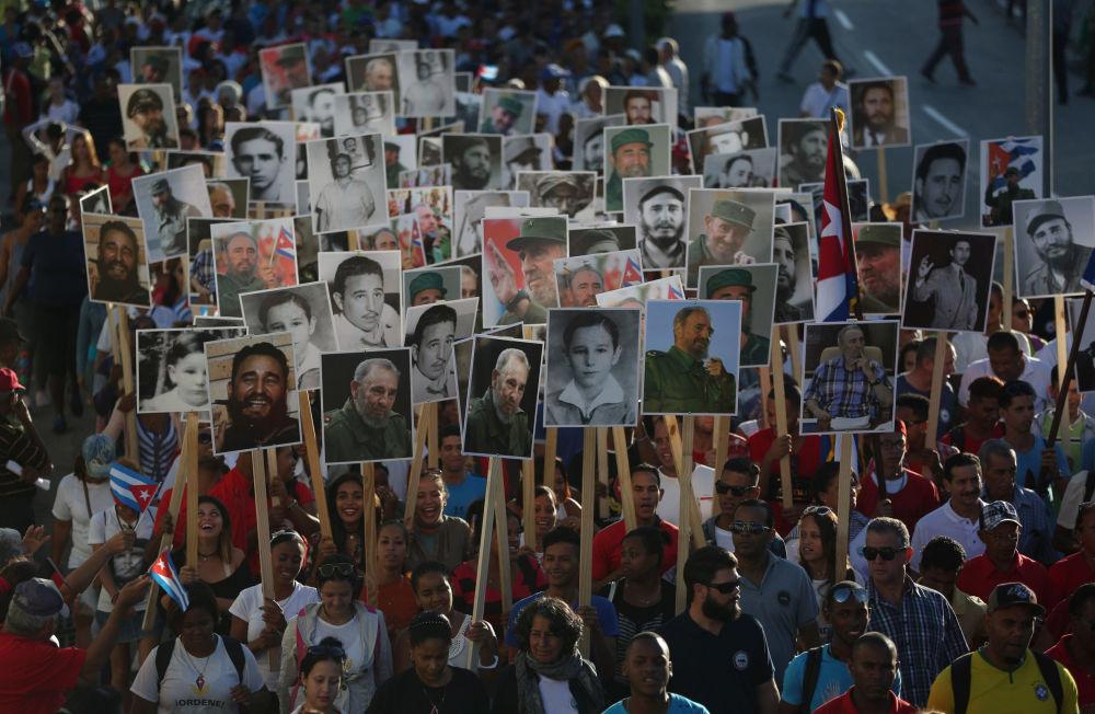 Pessoas com cartazes de Fidel Castro marcham pelas ruas de Santiago de Cuba em memória do dia em que o líder cubano foi enterrado