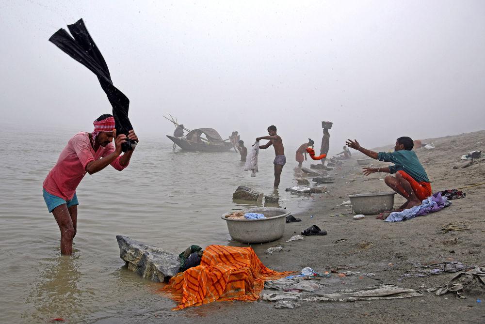 Pessoas lavam roupa no rio Brahmaputra, Índia