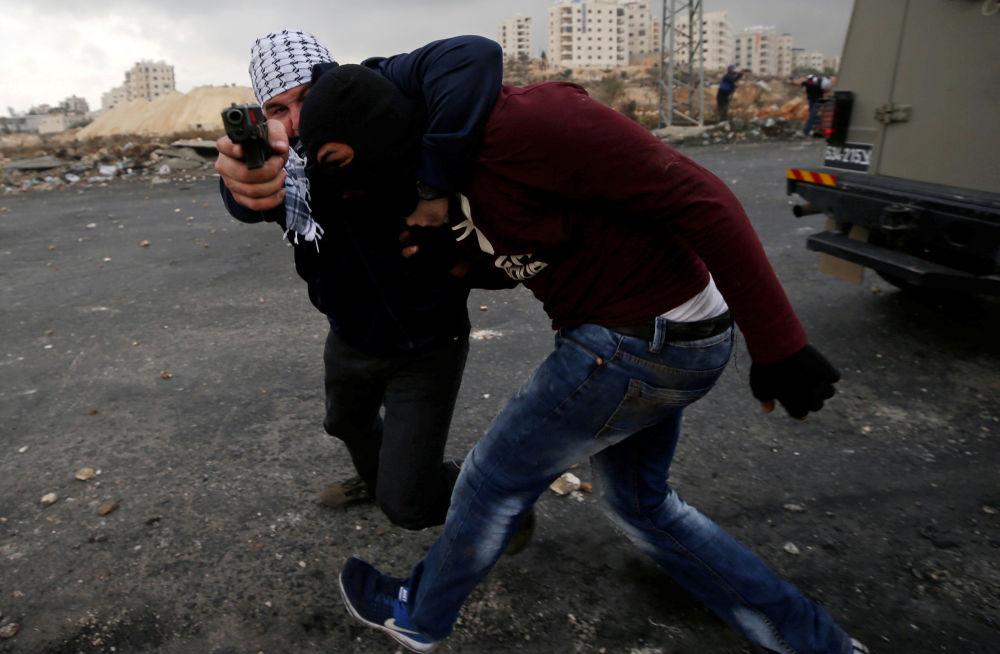 Um agente da inteligência israelense à paisana detém um manifestante palestino durante os protestos perto do povoado judeu de Beit El, a pouca distância da cidade de Ramallah, na Cisjordânia, em 13 de dezembro de 2017