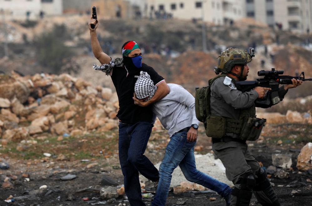Agentes dos serviços secretos israelenses que trabalham à paisana detêm um manifestante palestino perto do povoado de Beit El, a pouca distância da cidade de Ramallah, na Cisjordânia, em 13 de dezembro de 2017