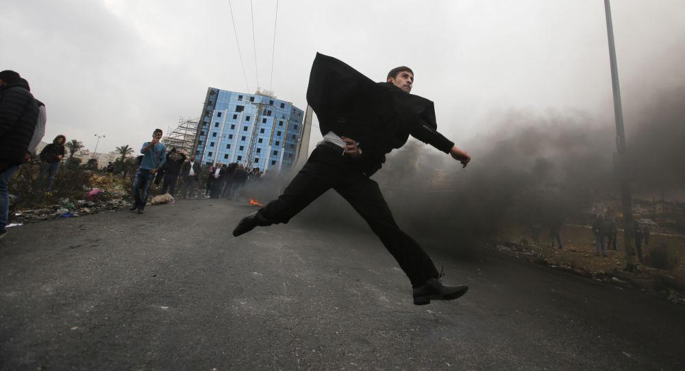 Um advogado palestino atira pedras em direção às tropas israelenses durante confrontos perto do povoado de Beit El, a pouca distância da cidade de Ramallah, na Cisjordânia, em 13 de dezembro de 2017