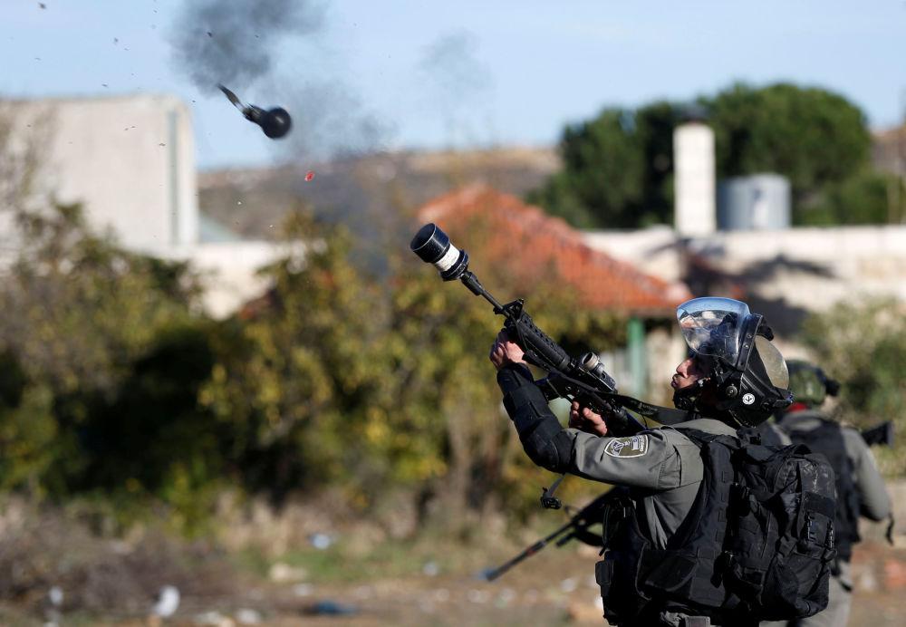 Um guarda fronteiriço israelense lança gás lacrimogêneo contra os manifestantes palestinos durante os confrontos provocados pela decisão de Donald Trump de reconhecer Jerusalém como capital do Estado judeu, em 9 de dezembro de 2017
