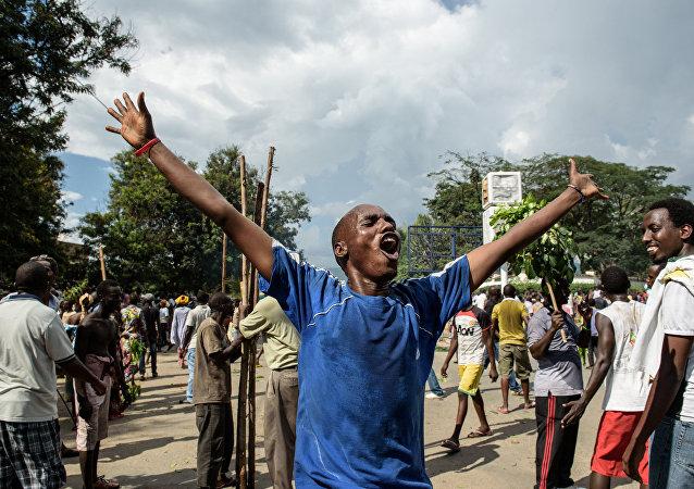 Homem comemora após anúncio da destituição do presidente Pierre Nkurunziza