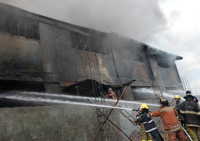 Bombeiros tentam apagar as chamas em fábrica de chinelos de Manila