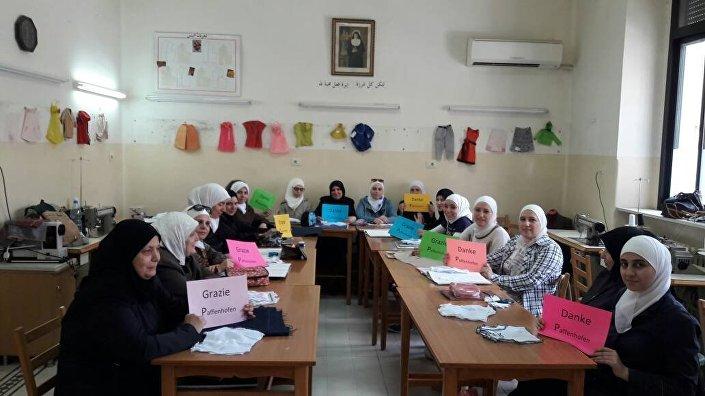 Mulheres síras agradecendo aos organizadores de cursos de costura
