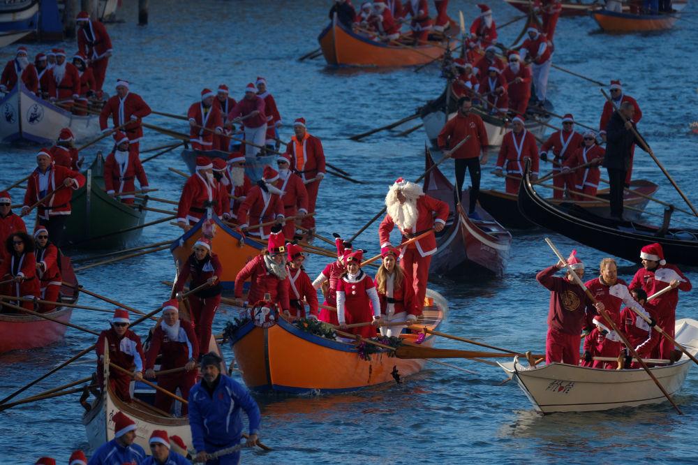 Pessoas vestidas de Papais Noéis durante a regata natalina em Veneza, na Itália, em 17 de dezembro de 2017