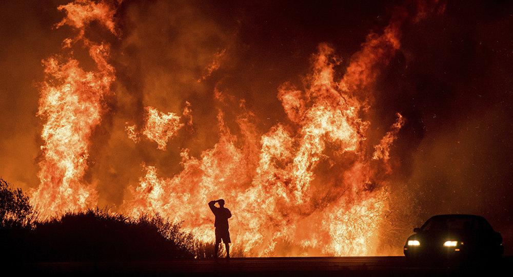 Um motorista na Highway 101 assiste as chamas do incêndio Thomas, ao norte de Ventura, na Califórnia, em 6 de dezembro de 2017.