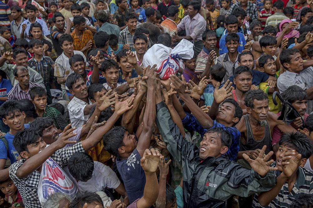 Segundo a organização Médicos Sem Fronteiras (MSF), ao menos 6.700 pessoas foram mortas pelo exército de Mianmar - que persegue os muçulmanos de etnia Rohingya no país. A violência causou o deslocamento forçado de milhares deles para os países vizinhos. Na foto, membros de um campo de refugiados em Bangladesh disputam alimentos.