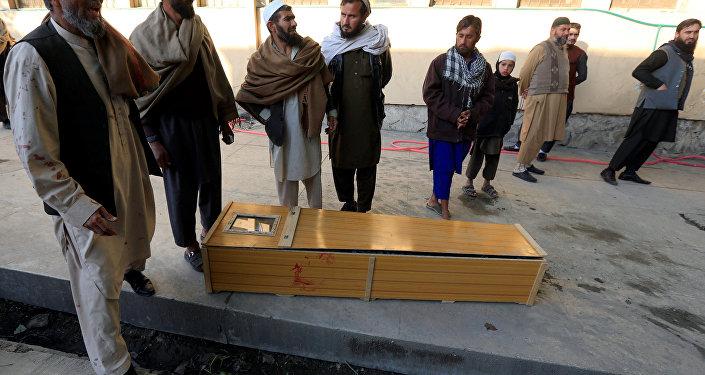 Pessoas perto de um caixão de uma vítima do atentado que se deu em Jalalabad, no Afeganistão, em 31 de dezembro de 2017