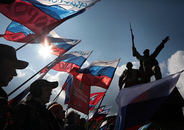 Pessoas balançam bandeiras russas durante celebração do 3º aniversário da Crimeia como parte do território russo, Sevastopol (foto de arquivo)