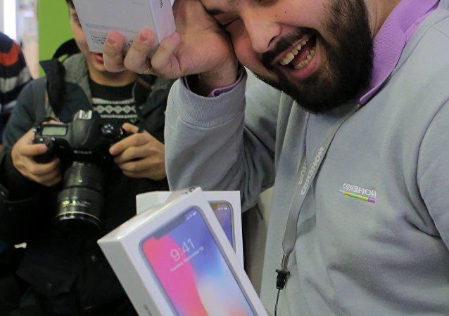 Vendedor durante início da venda do iPhone X em Moscou