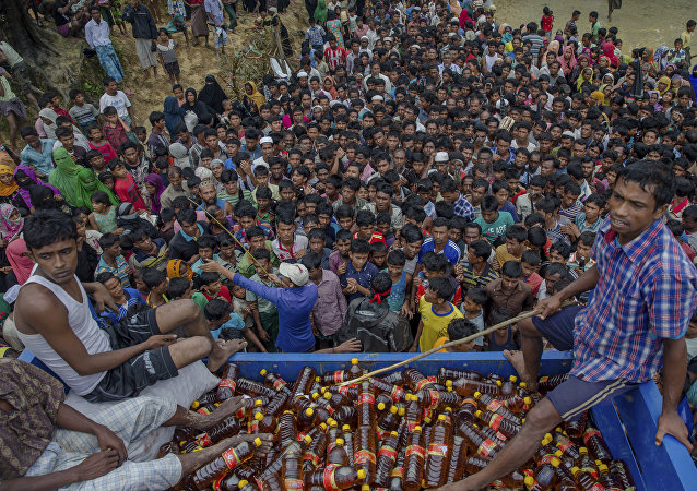 Rohingya Muslims, who crossed over from Myanmar into Bangladesh, wait during distribution of food items near Kutupalong refugee camp, Bangladesh, Tuesday, Sept. 19, 2017.