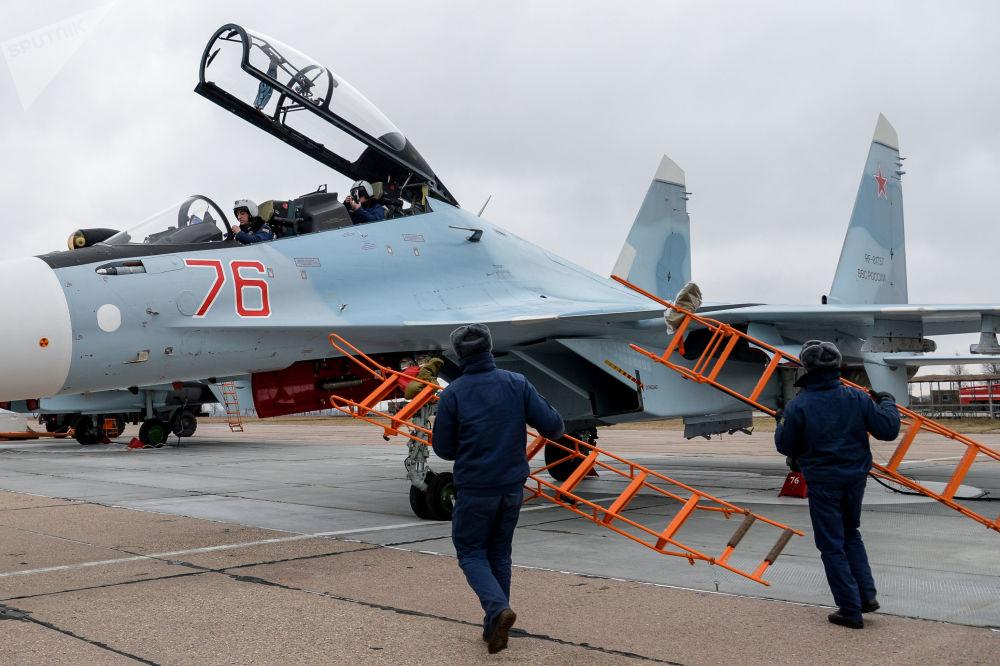 Pilotos do Distrito Militar Ocidental da Rússia preparam-se para o voo na cabina de um caça multifuncional Su-30SM, no polígono de Voronezh