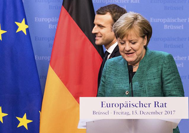 Presidente francês, Emmanuel Macron, à esquerda, passa por detrás da Chanceler alemã, Angela Merkel, que se prepara para falar durante conferência de imprensa no encontro da União Europeia, em Bruxelas, na sexta-feira, 15 de dezembro, de 2017.