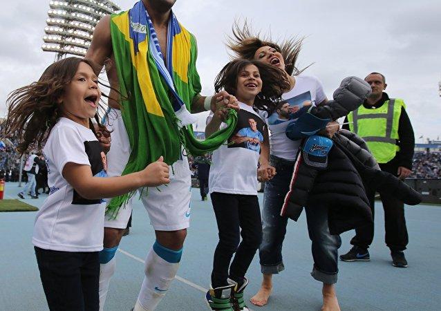 Enrolado na bandeira do Brasil, Hulk comemorou o título russo com a esposa e as filhas.