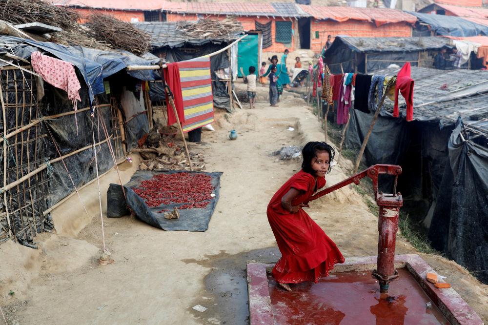 Menina refugiada rohingya tira água com uma bomba hidráulica no campo de Palong Khali, no Bangladesh